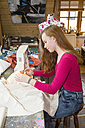 Female teenager using sewing machine in a workshop - SARF001613