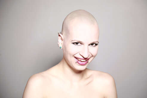 Smiling young woman with bald head and piercings - VE000034