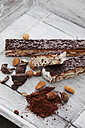 Italian bars of nougat, almond, hazelnut, cocoa powder, chocolate on wooden tray - CSF024746