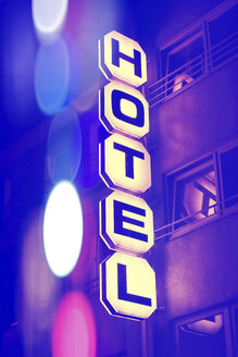 Germany, Duesseldorf, facade of hotel with lighted sign at night - HOHF001299