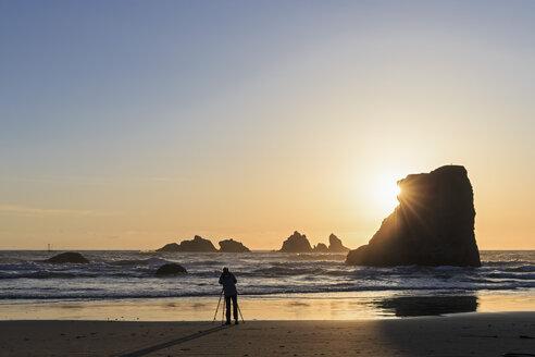 USA, Oregon, Bandon, Bandon Beach, Rocky needles at sunset, female fotographer at beach - FOF007782