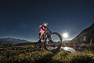 Austria, Altenmarkt-Zauchensee, young woman riding mountain bike at sunrise - HHF005180