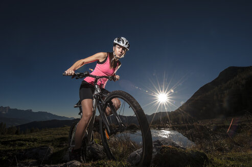 Austria, Altenmarkt-Zauchensee, young woman riding mountain bike at sunrise - HHF005181