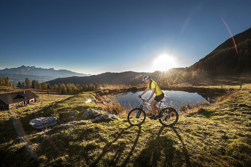 Austria, Altenmarkt-Zauchensee, young woman riding mountain bike at sunrise - HHF005187