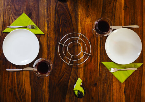 Laid wood table with plates and red wine - KRPF001341