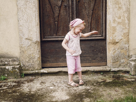 Italy, Tuscany, Montefollonico, girl at wooden door - GSF000983