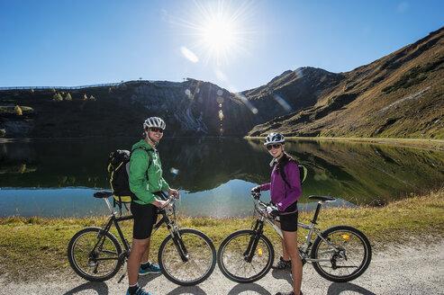 Austria, Altenmarkt-Zauchensee, young couple with mountain bikes at mountain lake - HHF005200
