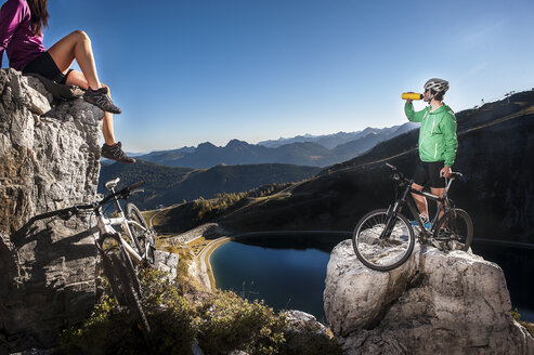 Austria, Altenmarkt-Zauchensee, young couple with mountain bikes in the mountains - HHF005210