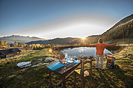 Austria, Altenmarkt-Zauchensee, young woman in the mountains at sunrise - HHF005126
