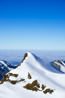 Germany, Bavaria, Allgaeu, Allgaeu Alps, couple standing on summit in winter - WGF000619