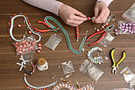 Young woman working on self-made jewelry - BFRF001006
