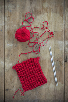 Red ball of wool and knitting on wood - CRF002637