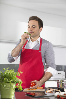 Portrait of man with red apron standing in kitchen smelling basil - PDF000832