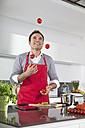 Smiling man juggling with tomatoes in kitchen - PDF000835