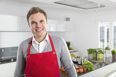 Portrait of smiling man with red apron in kitchen - PDF000841