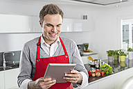 Smiling man looking at digital tablet in the kitchen - PDF000844