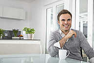 Smiling man sitting in kitchen with cup of coffee - PDF000847