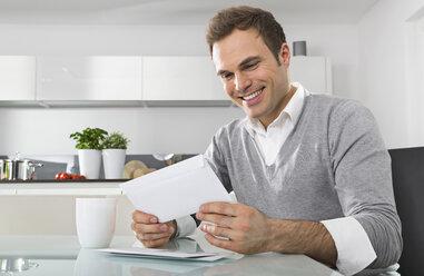 Smiling man sitting in kitchen watching envelope - PDF000853