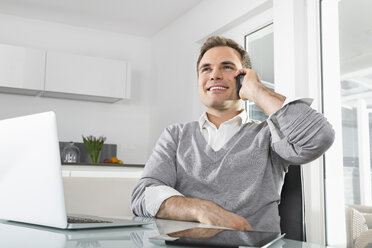 Smiling man sitting in kitchen with laptop and digital tablet telephoning with smartphone - PDF000856