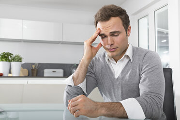 Man with closed eyes sitting in kitchen with hand on his face - PDF000859