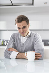 Portrait of smiling man sitting in kitchen with cup of coffee - PDF000862