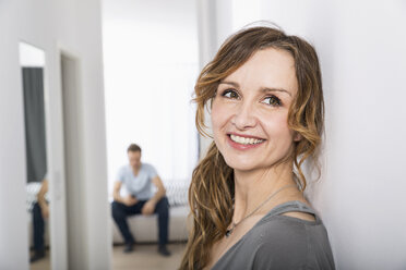 Portrait of smiling woman standing in corridor while man waiting in the background - PDF000871