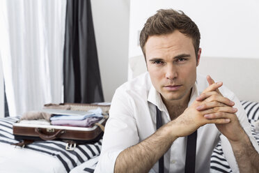 Businessman sitting on bed with clasped  hands - PDF000874
