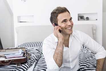 Smiling businessman sitting on bed telephoning with smartphone - PDF000893