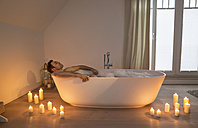Man relaxing in bathtub with lighted candles arround - PDF000876