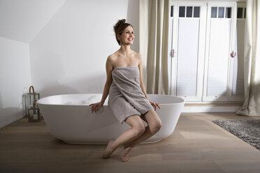 Smiling woman sitting on the edge of modern bathtub drinking champagne - PDF000879