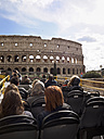 Italy, Rome, Tourists doing sightseeing tour in tour bus, passing Colosseum - LA001360