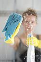 Woman cleaning glass pane - CHPF000095
