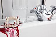Bloody vampire dentures on bathroom sink - STK001205
