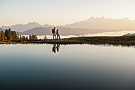 Austria, Altenmarkt-Zauchensee, young couple at mountain lake in the Lower Tauern - HHF005142