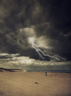 France, Contis-Plage, man standing at beach, thunderstorm and lightning, digitally manipulated - DWI000448