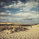 France, Contis-Plage, man walking along the dunes - DWIF000453