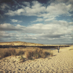 France, Contis-Plage, man walking along the dunes - DWIF000453