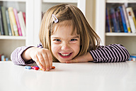 Smiling little girl playing with chocolate buttons - LVF003029