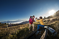 Austria, Altenmarkt-Zauchensee, young couple taking picture on hiking trip at Niedere Tauern - HHF005133