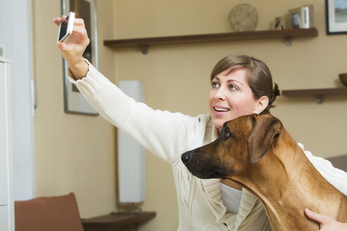 Woman taking selfie with her Rhodesian Ridgeback dog - JTLF000052