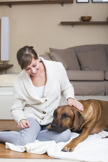 Woman caressing her Rhodesian Ridgeback dog - JTLF000055