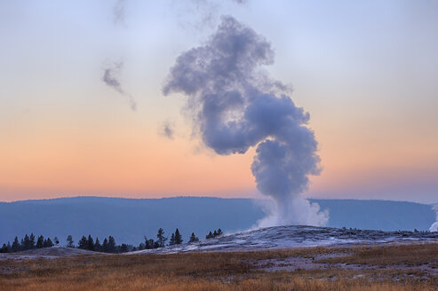 USA, Wyoming, Yellowstone National Park, Old Faithful Geyser erupting at sunset - RUEF001582