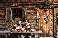 Austria, Altenmarkt-Zauchensee, couple having a break at alpine cabin - HHF005148