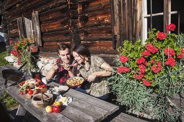 Austria, Altenmarkt-Zauchensee, couple having a break at alpine cabin - HHF005151