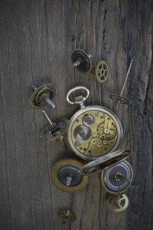 Old pocket watch and cogwheels on dark wood - CRF002648