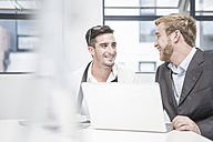 Two smiling businessmen having an office meeting - ZEF004523