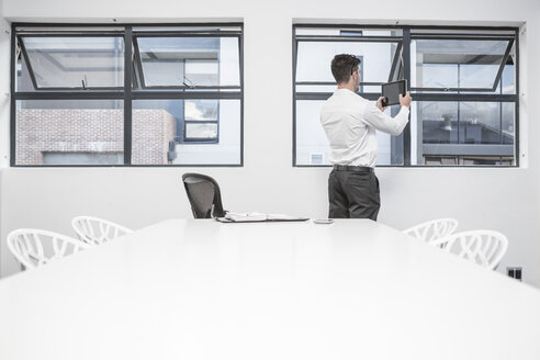 Businessman in meeting room holding digital tablet at the window - ZEF004526