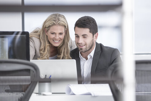Smiling businessman and businesswoman in office looking at laptop - ZEF004659
