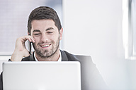 Smiling businessman in office with laptop and cell phone - ZEF004665