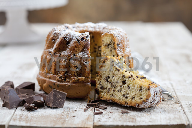Sliced chocolate cake sprinkled with icing sugar and pieces of chocolate on wood - CSF024914